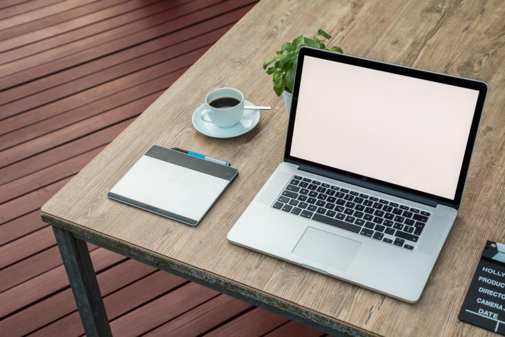 パソコンとコーヒーが置いてあるテーブルの画像