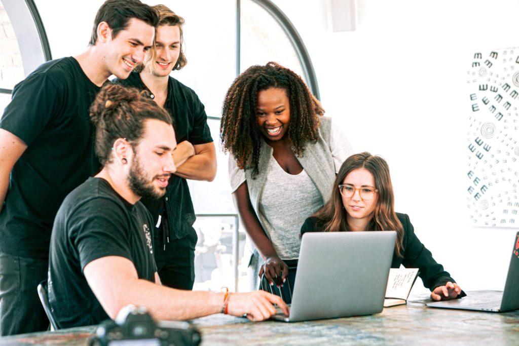 男女数名が笑顔でパソコンを囲む様子の画像