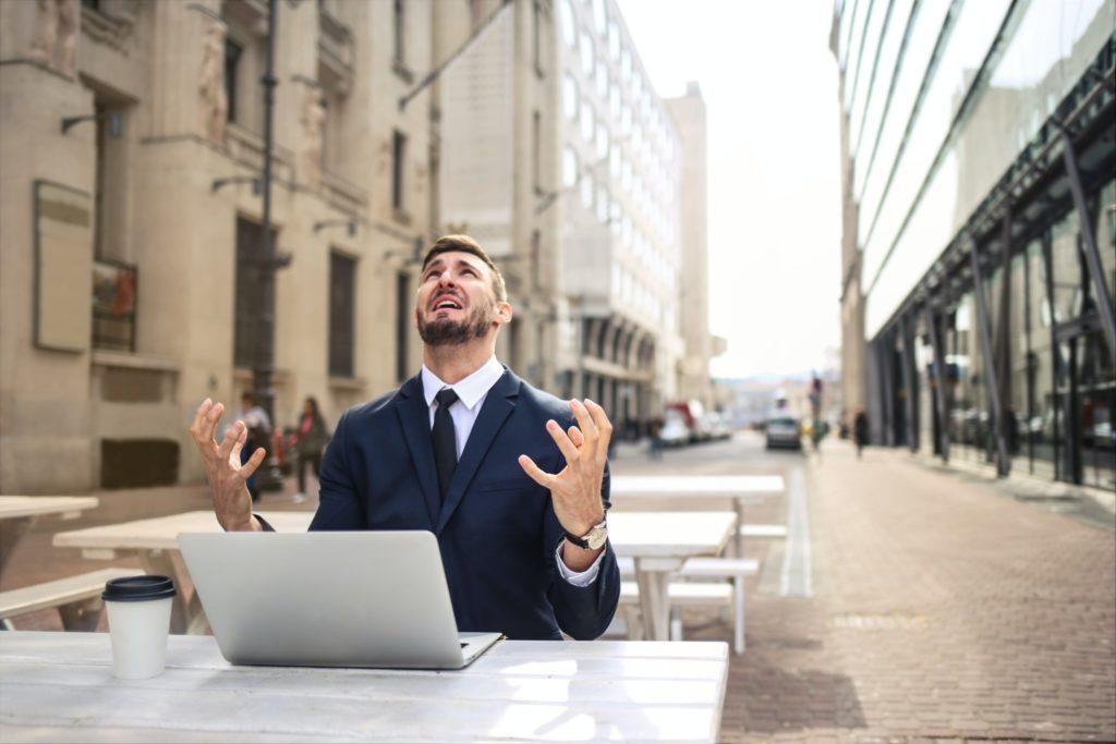 パソコンの前で絶望的な表情をしている男性の画像